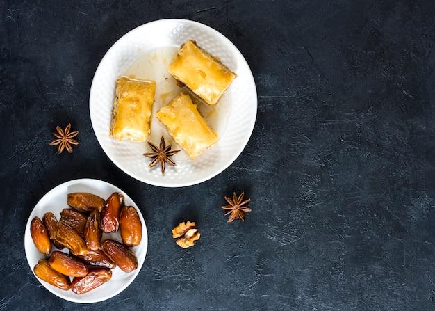 黒いテーブルの上の日付フルーツと東部のお菓子