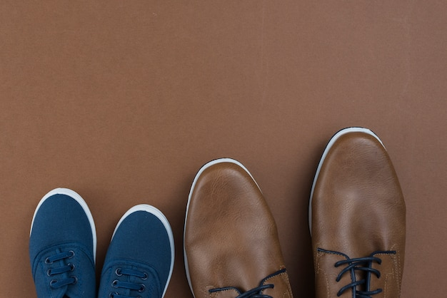 茶色のテーブルの上の男と子の靴