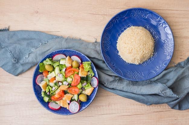 Приготовленный рис с овощным салатом на светлом столе