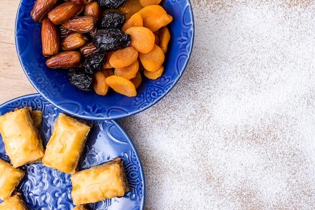 Различные сухофрукты с восточными сладостями на голубых тарелках