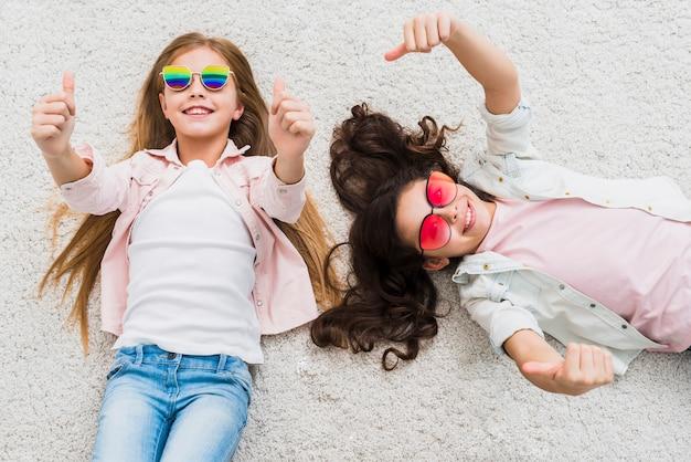 Поднятый вид двух подруг, лежа на ковре, показывая большой палец вверх знак