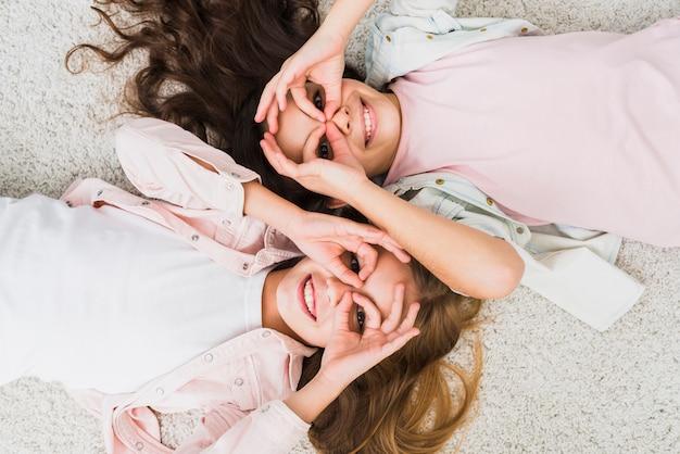 Возвышенный вид девушек, лежащих на ковре, делающих хорошо жест, как бинокль