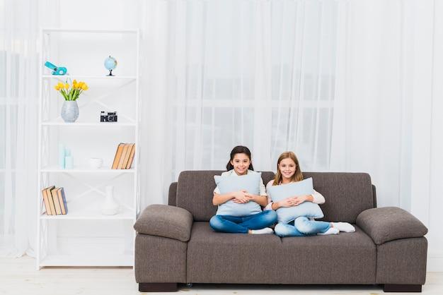 Улыбающиеся две девушки сидят на диване с подушкой в современной гостиной