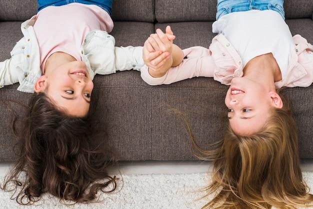 彼女の頭を上下逆さまにソファーに横になっている幸せな女友達