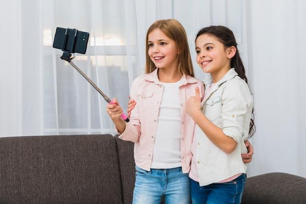 Улыбающаяся девушка показывает большой палец вверх знак, принимая автопортрет с подругой
