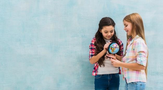 Улыбающиеся две девушки, стоящие у синей стены, смотрящие на маленький глобус