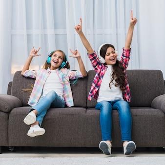 Расслабленные красивые две девушки наслаждаются музыкой на наушниках, поднимая руки, танцуя