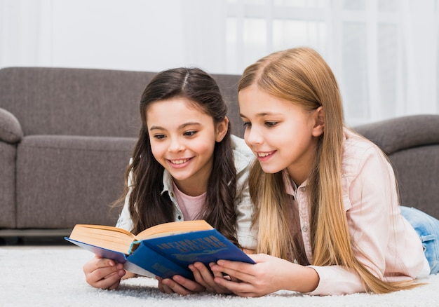 Две красивые девушки лежат на ковре, читая книгу вместе дома