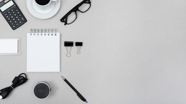 電卓に囲まれた空白のスパイラルメモ帳。ティーカップペーパークリップ;スピーカー;ペン;灰色の背景上のケーブルと眼鏡