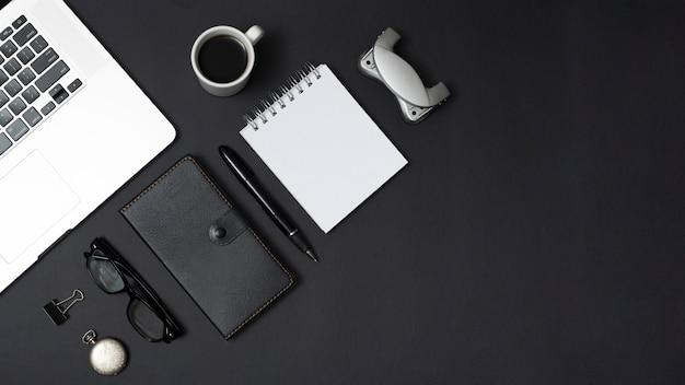 オフィス文具と黒の背景上の紅茶のカップとパーソナルアクセサリーのラップトップ