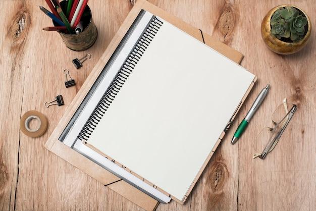 空白のスパイラル本の平面図。メガネ。テーブルの上の植物および事務用品