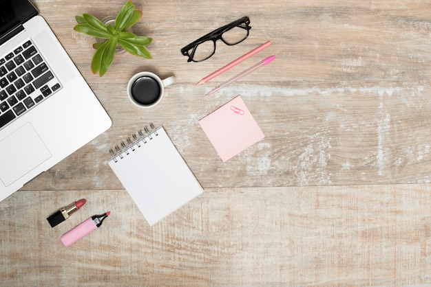 ラップトップの立面図。口紅;蛍光ペンスパイラルメモ帳。コーヒーカップ;ペン;と木製のテーブルの上の眼鏡