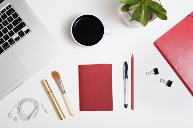 ノートパソコンの平面図。コーヒーカップ;イヤホンそしてペン。化粧用ブラシ;マスカラ;白い背景の上の鉢植えの植物