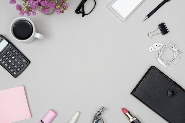 化粧品のハイアングル。事務用文房具;コーヒーカップ;灰色の背景に配置された眼鏡