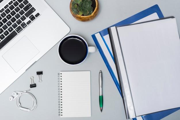ノートパソコンの平面図。フォルダコーヒーカップ;イヤホンスパイラルメモ帳と灰色の背景に対してペン