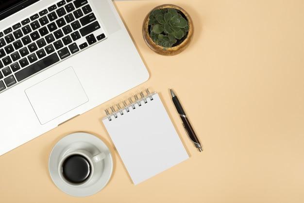 ラップトップの立面図。コーヒーカップ;ペン;とベージュ色の背景上のスパイラルメモ帳