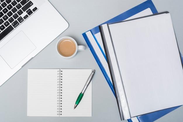 コーヒーカップとビジネスフォルダー。ノートパソコンとオープンスパイラルメモ帳。グレーのテーブルの上にペン
