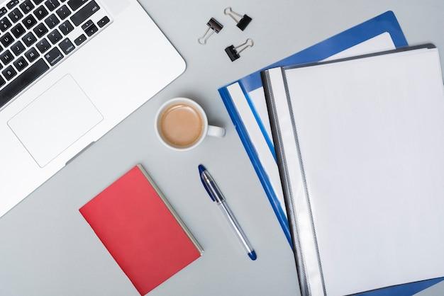 コーヒーカップの高角度のビュー。ノートパソコンフォルダーと灰色の背景上のラップトップとペーパークリップ