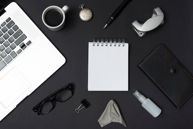 ノートパソコンと事務用品のオーバーヘッドビュー。コーヒーカップ;めがね黒いデスクトップに対するペン