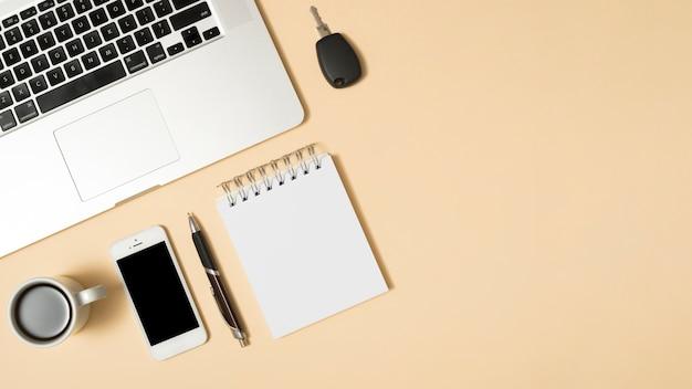 コーヒーカップ付きラップトップ。携帯電話;そして空白の日記。ベージュ色の背景に対してペン