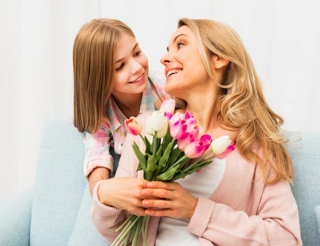 Довольная мама с тюльпанами смотрит на дочь