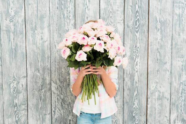 バラの花束で顔を隠して女の子