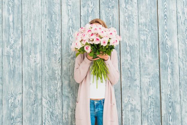 バラの花束で女性の顔を閉じる