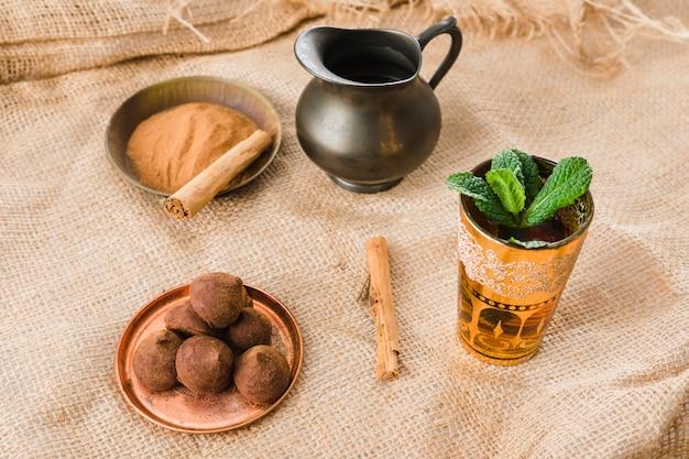 レトロなピッチャー、シナモン、しわのある黄麻布の上のお菓子の近くのカップ