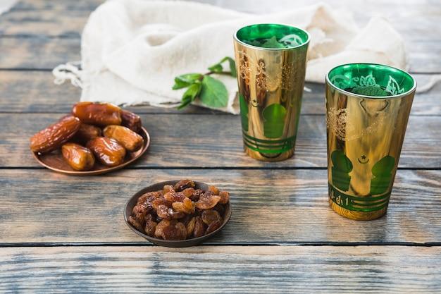 Кружки напитка возле сухофруктов на блюдцах и текстиле