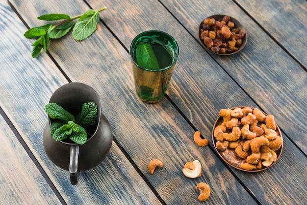 Чашка возле кувшина с растением и сухофруктами и орехами