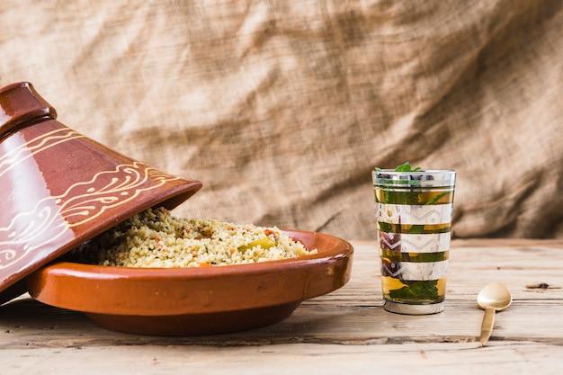 テーブルの上のカップの近くのキノアのサラダ