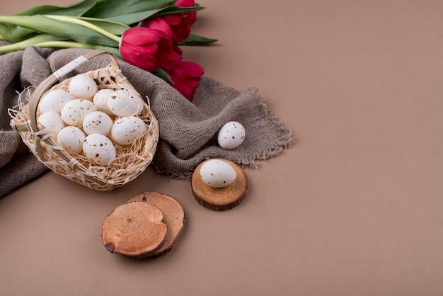赤いチューリップが付いているバスケットの白い鶏の卵