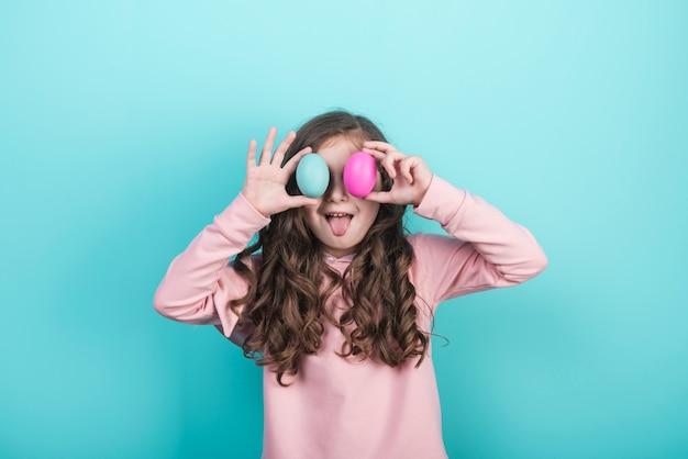 Маленькая девочка держит пасхальные яйца на глазах