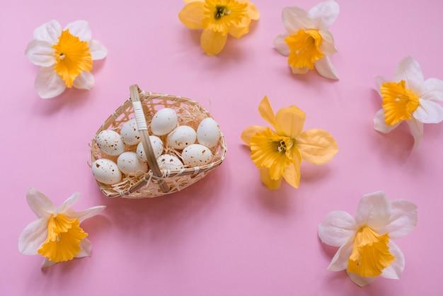 黄色の花が付いているバスケットの白い鶏の卵