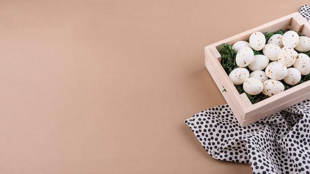 Белые куриные яйца в деревянной коробке