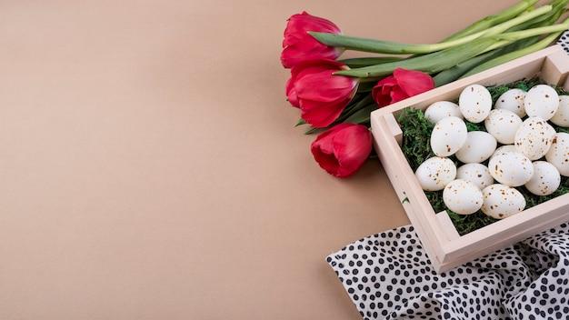 Белые куриные яйца в коробке с тюльпанами