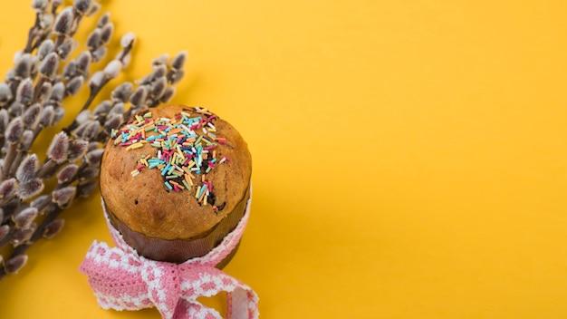 黄色のテーブルに柳の枝とイースターケーキ