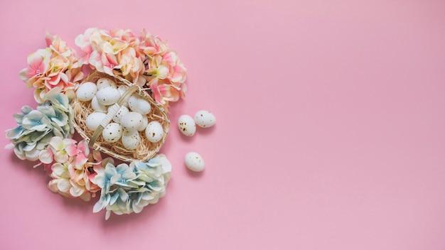 花が付いているバスケットの白い鶏の卵