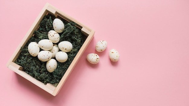 ピンクのテーブルの上のボックスに白い鶏の卵