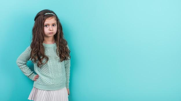 Обиженная маленькая девочка держит руку на талии