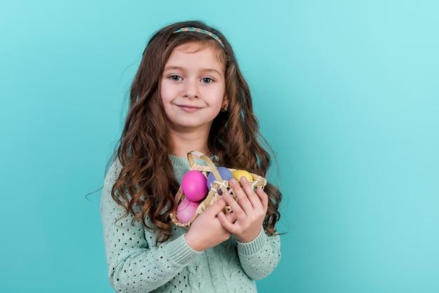 Маленькая девочка держит корзину с пасхальными яйцами