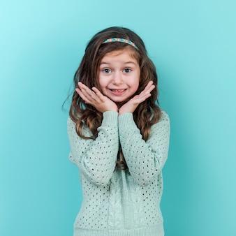 Изумленная маленькая девочка стоя на голубой предпосылке