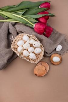 赤いチューリップの花のバスケットの白い鶏の卵