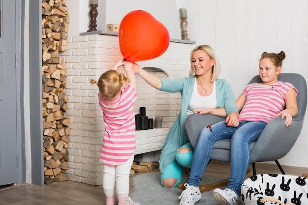 母と娘の赤いハート形風船を保持