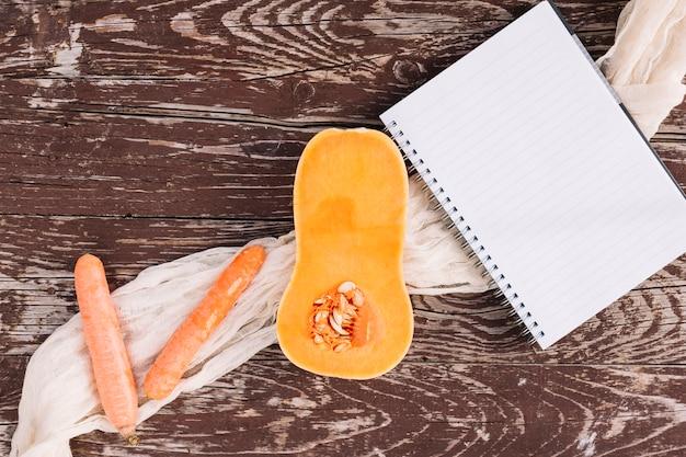 生の半分にした有機バタースカッシュ。ニンジンと木製のテーブル表面にスパイラルメモ帳