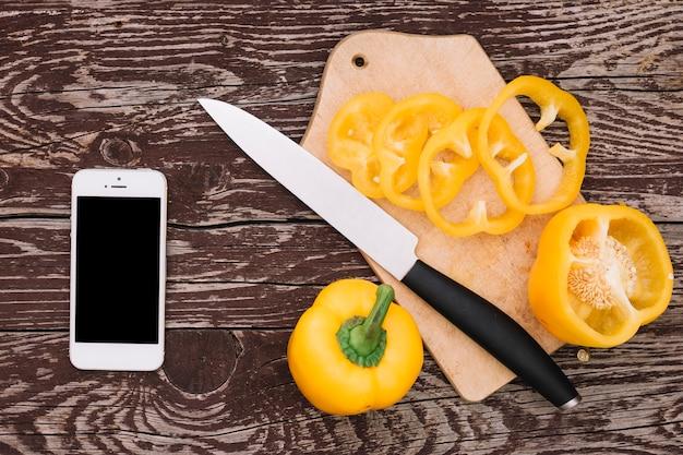 黄色ピーマンと木製の机の上のナイフと携帯電話