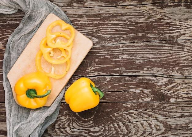 全体と木製の机に対して灰色の織物上まな板に黄色ピーマン