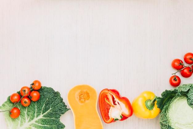 新鮮なチェリートマト。キャベツ;ピーマンとバターナットスカッシュ、木の表面