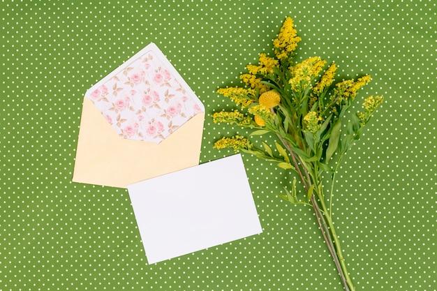 カードと黄色のアキノキリンソウの花の高角度のビュー。緑の織り目加工の背景上の封筒を開く