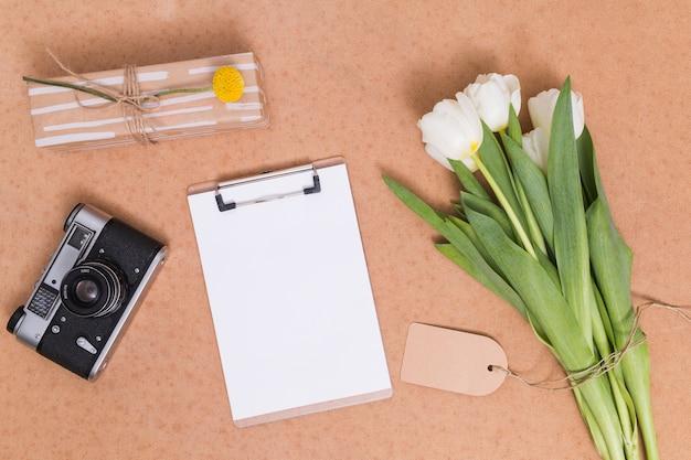 白いチューリップの花の束の立面図。レトロカメラギフト用の箱と机の上のクリップボードとホワイトペーパー